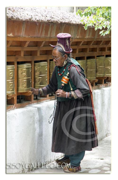 Típico atuendo de la zona y portando un rodillo de oración